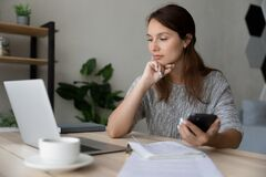 Free Thoughtful Confident Businesswoman Looking At Laptop Screen, Holding Smartphone Stock Photography - 221246312