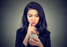 Thoughtful confused woman looking at her smart phone. Isolated on gray background Royalty Free Stock Images