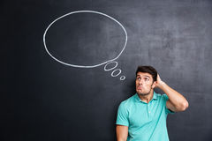 Thoughtful confused young man standing and thinking over blackboard background stock images