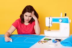 Thoughtful confused young seamstress looks at pattern on blue fabric on table, holding piece of chalk in one hand, having royalty free stock images
