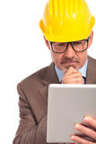 Thoughtful construction engineer reading on his tablet pad Royalty Free Stock Image