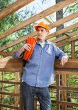 Thoughtful Construction Worker Carrying Rolled Stock Image