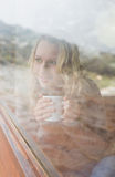 Thoughtful content woman with coffee cup looking out through window Royalty Free Stock Image