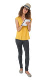 Thoughtful cool young woman writing in notepad Royalty Free Stock Photos