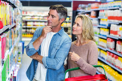 Thoughtful couple choosing a product Royalty Free Stock Photo