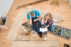 Thoughtful Couple With Disassembled Furniture. Portrait Of Thoughtful Couple With Disassembled Furniture Parts In New Home Stock Photography
