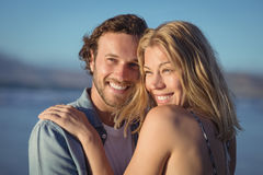 Thoughtful couple hugging at beach. During sunny day Royalty Free Stock Image