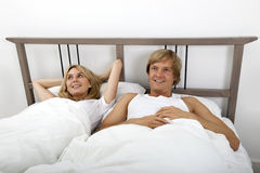Thoughtful couple lying in bed at home Royalty Free Stock Photography