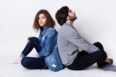 Thoughtful couple sitting on the floor back having rest. A young female dressed in jean clothes and stylish guy dressed casual clo. Thes relaxing on the floor Royalty Free Stock Image