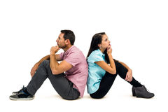 Thoughtful couple sitting on the floor back to back with hands on chins. On white screen Royalty Free Stock Images