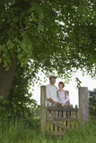Thoughtful Couple Standing Across Field Gate Stock Photography