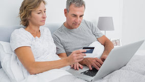 Thoughtful couple using their laptop to buy online Royalty Free Stock Photography