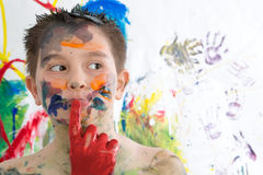 Thoughtful creative little boy covered in paint. Standing with his finger to his lips looking contemplatively to the side in front of his contemporary artwork stock image