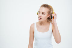 Thoughtful curious young woman taking off yellow headphones Stock Image