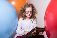 Thoughtful curly teen girl in glasses with wooden abacus on the Stock Photography