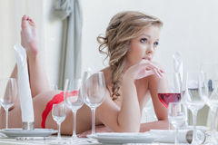 Thoughtful curvy woman lies with glass of wine Royalty Free Stock Photo