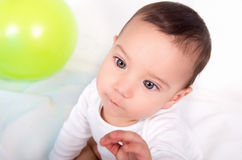 Thoughtful cute baby boy with an intense. Thoughtful blue eyed baby boy with an intense concentrated look in white background and green ballon Royalty Free Stock Photos