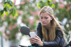 Thoughtful cute blonde girl on a scooter using cell phone Royalty Free Stock Photo