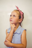 Thoughtful cute girl with hand on chin in classroom Stock Images