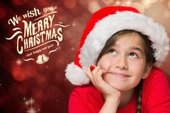 Thoughtful cute girl in santa hat with hand on chin Royalty Free Stock Photo