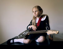 Thoughtful cute little girl with a guitar sitting on the floor Royalty Free Stock Image