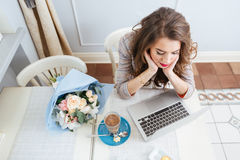 Thoughtful cute woman using laptop and thinking in cafe Royalty Free Stock Photography