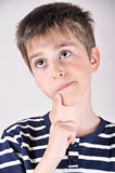 Thoughtful cute young boy looking up Stock Image