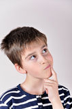 Thoughtful cute young boy looking up Royalty Free Stock Photos