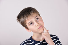 Thoughtful cute young boy looking up Stock Photo