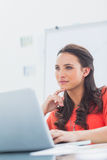 Thoughtful designer sitting behind her desk Royalty Free Stock Photography