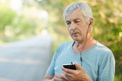 Thoughtful determined wrinkled mature male holds modern smart phone, listens pleasant melody in earphones, dressed in casual t shi Royalty Free Stock Photography