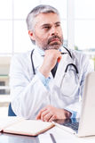 Thoughtful doctor. Thoughtful mature grey hair doctor holding hand on chin and looking away while sitting at his working place Royalty Free Stock Photo