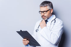 Thoughtful doctor. Thoughtful mature doctor holding hand on chin and looking at his clipboard while standing against grey background Royalty Free Stock Photo