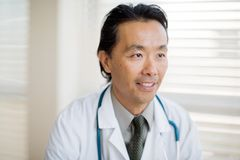 Thoughtful Doctor Smiling In Clinic Stock Photography