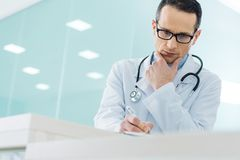 Thoughtful doctor in white coat with stethoscope writing diagnosis. In hospital stock image