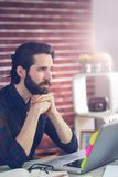 Thoughtful editor with hand clasped using laptop Stock Photo