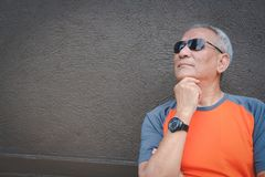 Thoughtful elder man wearing sunglasses standing near wall. elde. Thoughtful elder man wearing sunglasses standing near brown wall. asian elderly male thinking Royalty Free Stock Images