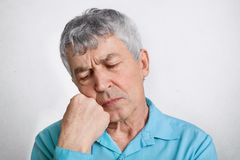 Thoughtful elderly male with pensive expression, feels lonely, keeps hand under chin and contemplates about his life, keeps eyes s royalty free stock images