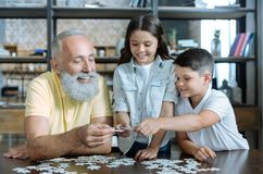 Thoughtful elderly man and grandchildren putting puzzle together. Help is what really matters. Selective focus on hands of a retired gentleman and his grandkids stock photos
