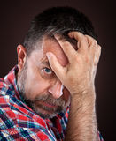 Thoughtful elderly man with hand near the face Stock Photo
