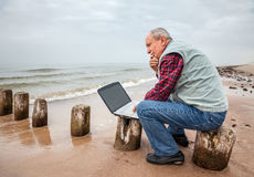 Thoughtful elderly man with the laptop Stock Images