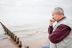 Thoughtful elderly man standing on the beach. On a foggy day royalty free stock images
