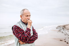 Thoughtful elderly man standing on the beach. On a foggy day royalty free stock photo