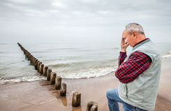Thoughtful elderly man standing on the beach Stock Photography