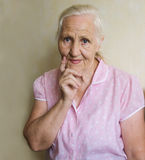 Thoughtful elderly woman. Portrait of a lovely old female thinking and looking forward royalty free stock images