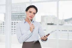 Thoughtful elegant businesswoman with clipboard in office Royalty Free Stock Photo