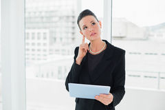 Thoughtful elegant businesswoman holding tablet PC. In a bright office Stock Photos