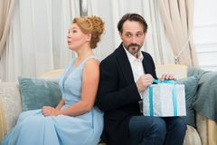 Thoughtful elegant woman sitting on sofa while her cheerful husband preparing a present royalty free stock images