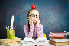 Thoughtful Elementary School Girl Study Photo. Cute Little Learner with Braid Sit Desk Think Question. Smart Caucasian Kid Hold Red Apple on Head. School royalty free stock images