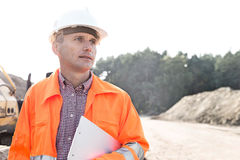 Thoughtful engineer holding clipboard against clear sky Stock Images